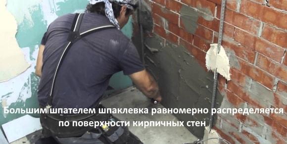 Большим шпателем шпаклевка равномерно распределяется по поверхности кирпичных стен